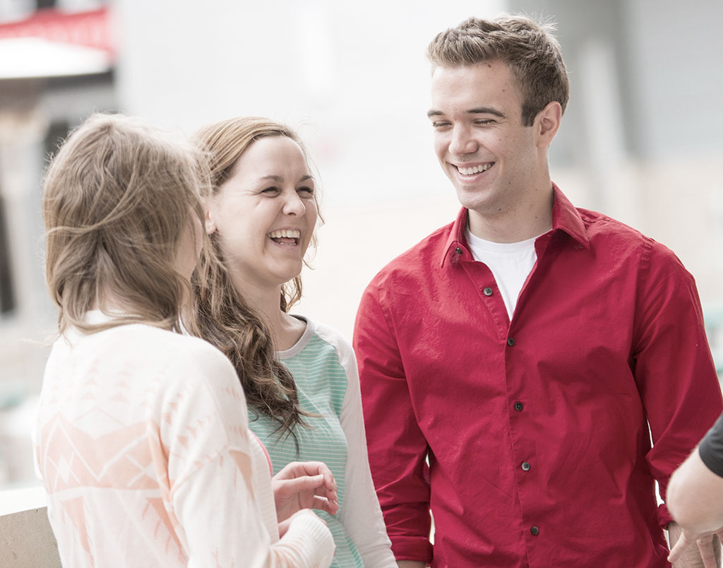 A photo of three students standing and talking