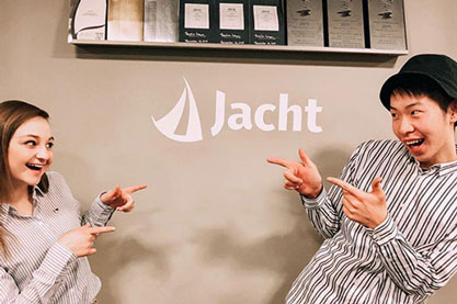 two students pointing at each other in front of Jacht logo