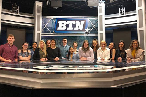 Students at desk in front of of BTN logo