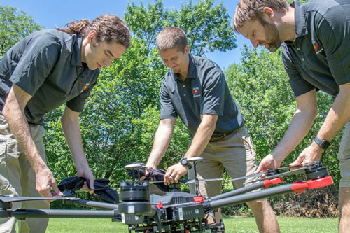 Three students working on a drone