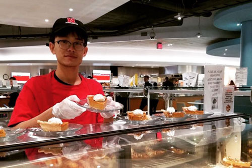 A student worker serving pumpkin pie in the dining hall