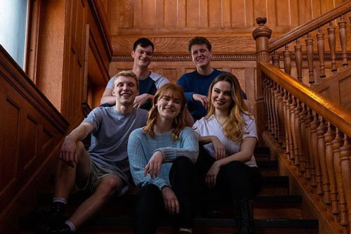 Theatre students sitting together on stairs
