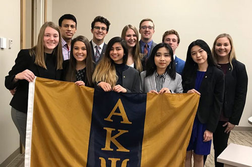 A group of students holding the Alpha Kappa Psi - Zeta flag